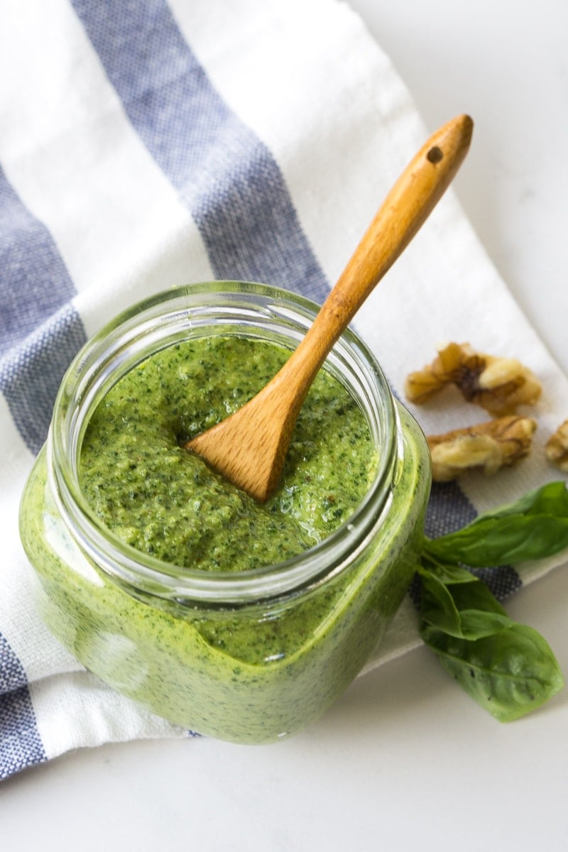 Vegan basil pesto in a jar with a spoon