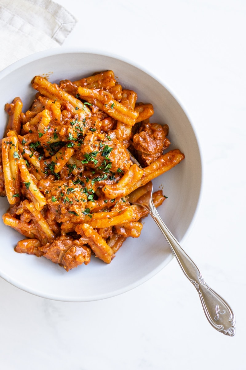 Spicy tomato pasta with fork in a bowl